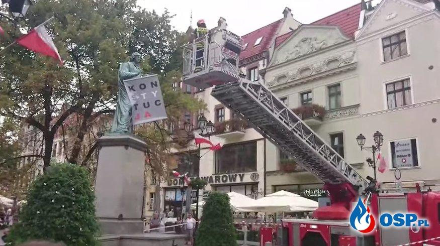 """Strażacy wezwani do zdjęcia baneru z napisem """"KONSTYTUCJA"""" z pomnika w Toruniu. OSP Ochotnicza Straż Pożarna"""
