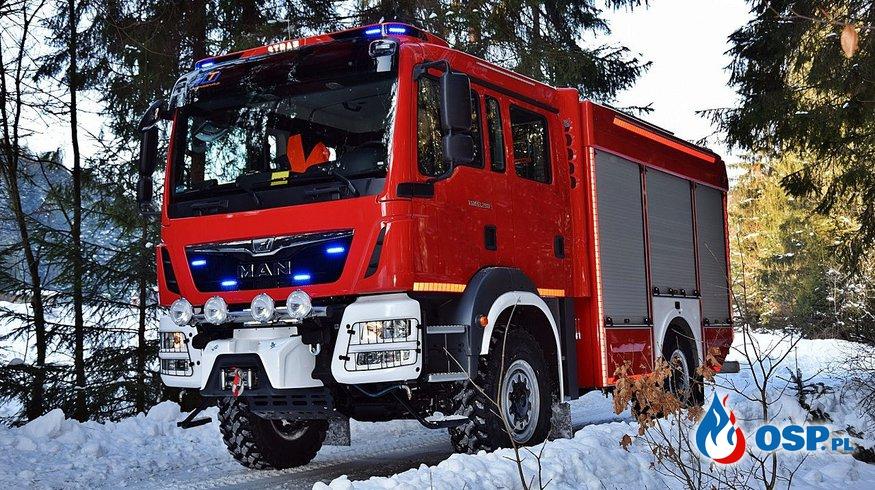 Nowy średni samochód pożarniczy jednym kołem w garażu. OSP Ochotnicza Straż Pożarna
